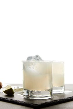 Close up view of refreshing caipirinha cocktails with lime and ice on tabletop on white