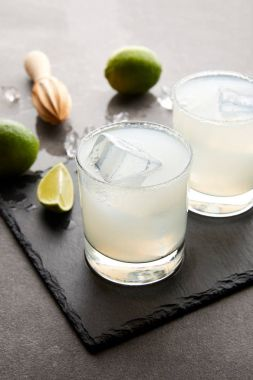 Close up view of wooden squeezer, refreshing margarita cocktails with lime and ice on grey tabletop