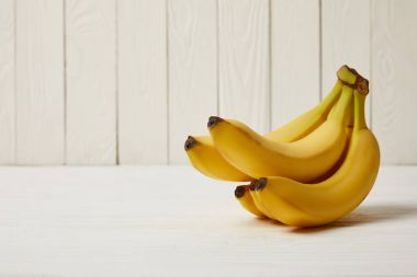 Raw organic yellow bananas on wooden background with copy space stock vector