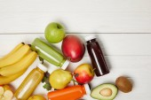 Fotografie top view of fresh fruits and smoothies on white wooden background with copy space