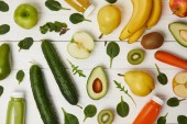 Fotografie flat lay with colorful fresh fruits and vegetables and bottles with smoothies on wooden background