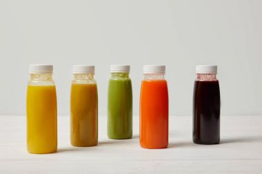colorful detox smoothies in bottles on white wooden surface