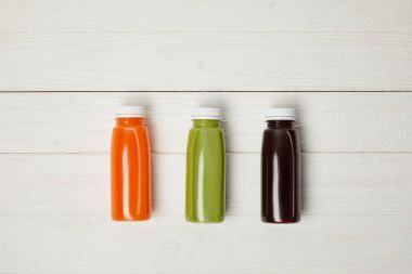 top view of bottles with detox smoothies in row on wooden background