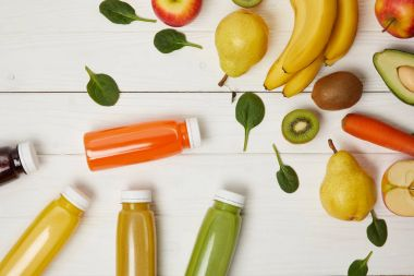 top view of fresh fruits and bottles with smoothies on wooden background