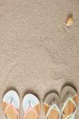 plochý ležela s letní žabky a mušle na písku