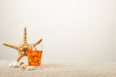 close up view of sea star, refreshing cocktail with straw and seashells on sand on grey background