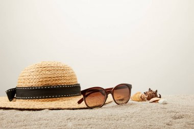 close up view of straw hat, sunglasses and seashells on sand on grey backdrop