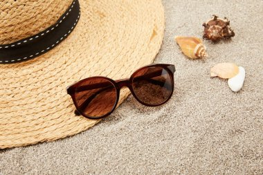 close up view of straw hat, seashells and sunglasses on sand