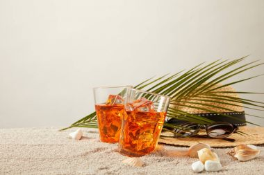 close up view of straw hat, cocktails, seashells, sunglasses and palm leaf on sand on grey backdrop