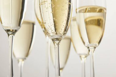 cropped image of champagne glasses with bubbles isolated on white background