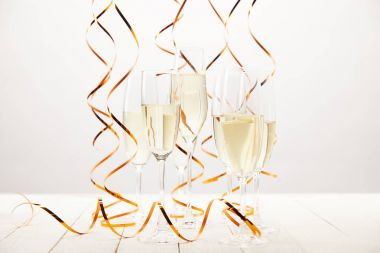 champagne glasses with ribbons on white wooden table, holiday concept