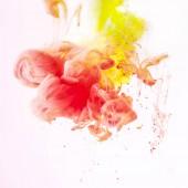 Fotografia spruzzi di vernice fumoso di giallo e rosso, isolato su bianco
