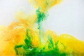 abstract texture with green and yellow paint flowing in water