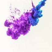 Fotografia fumosi spruzzi di vernice blu e viola in acqua, isolato su bianco