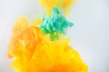 creative background with turquoise and orange paint flowing in water, isolated on grey
