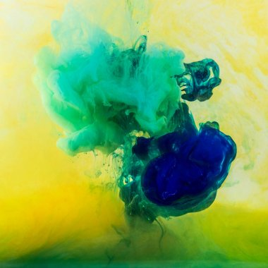 abstract swirls of green and blue paint flowing in yellow water