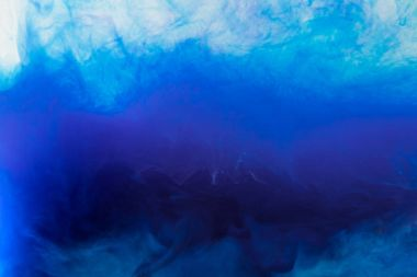 artistic background with flowing blue smoky paint in water