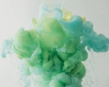 light background with mixing turquoise and green paint in water, isolated on grey