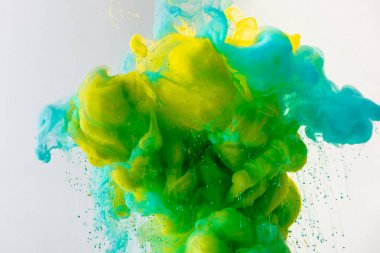 artistic background with flowing turquoise, yellow and green paint in water, isolated on grey