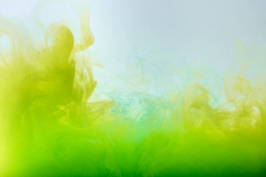 Abstract background with flowing yellow and green gouache paint in water stock vector