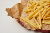 Photo close-up shot of delicious french fries on crumpled paper on white
