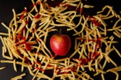 Fotografie top view of red apple surrounded with french fries poured with ketchup isolated on black
