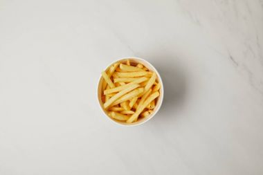 top view of bowl of french fries on white