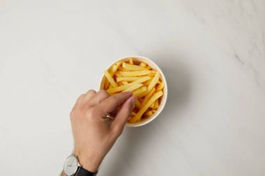 top view of man taking french fries from bowl on white