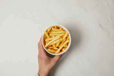 cropped shot of man holding bowl of delicious french fries on white