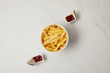 top view of french fries in bowl with containers of ketchup on white