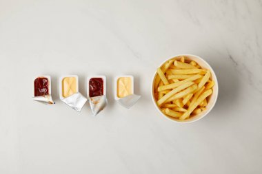 top view of french fries in bowl with containers of sauces in row on white