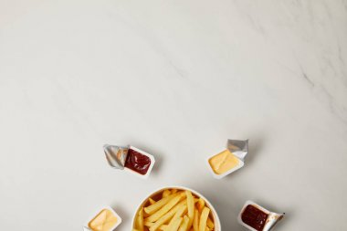 top view of french fries in bowl surrounded with containers of sauces on white