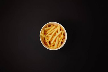 top view of delicious french fries in bowl isolated on black