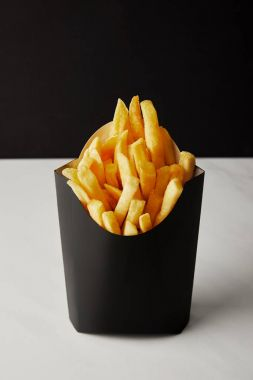 close-up shot of box of french fries on white marble surface isolated on black