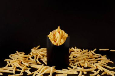 close-up shot of tasty french fries in black box surrounded with messy fries on tabletop isolated on black