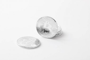 close-up shot of silver bitcoins on white tabletop