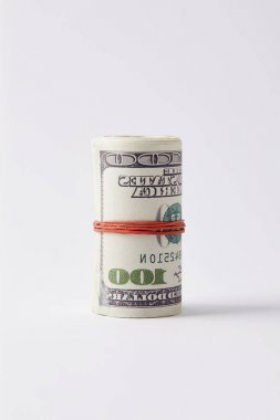 roll of dollars tied with rubber band on white surface
