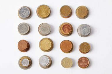 Top view of stacks of different coins on white stock vector