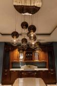 Lesklé kulové lustr nad elegantní dřevěný pult v kuchyni
