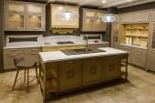 Interior of modern kitchen with beige cabinets