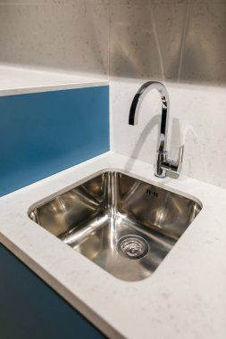 Close-up view of metal sink in renovated kitchen