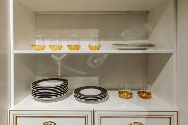 Stylish kitchen with modern tableware in cupboard