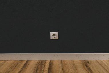 Single power socket in dark wall over wooden floor
