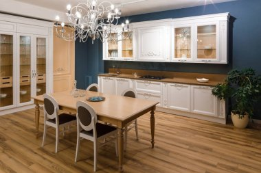 Table with chairs in stylish kitchen with chandelier