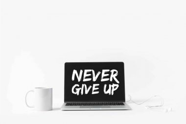 laptop with Never give up inspiration on screen, earphones and white mug, isolated on white
