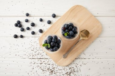 top view of chia puddings with fresh blueberries and mint on wooden cutting board on white surface