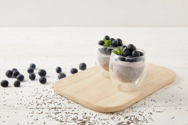 close up view of chia puddings with fresh blueberries and mint on wooden cutting board on white surface