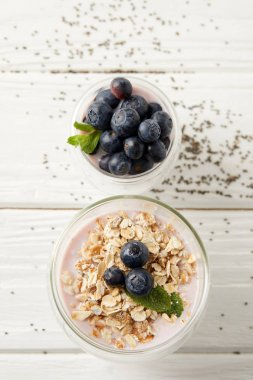 flart lay with arranged chia puddings with fresh blueberries, oatmeal and mint on white wooden tabletop