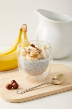 close up view of chia seed pudding with pieces of banana and hazelnuts on wooden cutting board with spoon