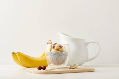 close up view of tasty chia seed pudding with bananas and hazelnuts on white tabletop